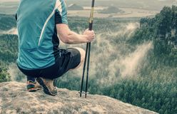 Man hiker legs in comfortable boots and poles stand on rock. royalty free stock photos