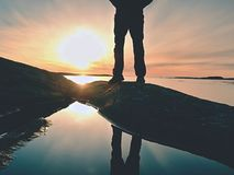 Man hiker legs in  high boots mirrored in water pool, sea with sunset sun. Tourist figure on rocky Stock Photography