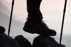Man hiker legs and poles stand on mountain peak rock. Man in mountains Stock Photos