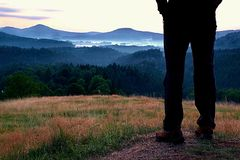 Man hiker legs in tourist boots stand on hill in the meadow. Sunrise above hills. Royalty Free Stock Photography
