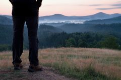 Man hiker legs in tourist boots stand on hill in the meadow. Sunrise above hills. Royalty Free Stock Image