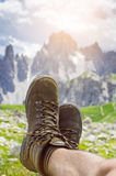 Man hiker lie on a ground. Peaks like a background. Sunny day.Trekking boots.Lens flare. Succesful backpacker enjoy a view. Stock Image