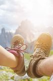 Man hiker lie on a ground. Peaks like a background. Sunny day.Trekking boots.Lens flare. Succesful backpacker enjoy a view. Stock Photos