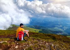 Hiker with red backpack is sitting on the top of mountain royalty free stock photography