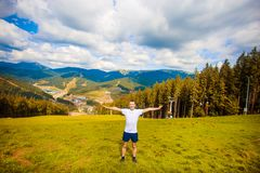 Man hiker relaxing on top of hill and admiring beautiful mountain valley view in summer stock images
