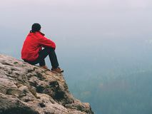 Man hiker sit on rocky summit. Hiker man take a rest on mountain peak. Man sit on sharp summit and enjoy spectacular view Stock Image