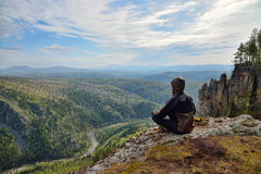 Man hiker sitting on top of mountain and contemplates beautiful view to the valley.  Stock Images