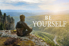 Man hiker sitting on top of mountain and contemplates beautiful view to the valley. Be Yourself lettering. Man hiker sitting on top of mountain and contemplates Royalty Free Stock Photography