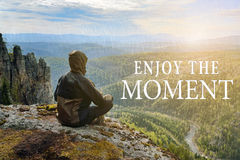 Man hiker sitting on top of mountain and contemplates beautiful view to the valley. Enjoy the Moment lettering. Man hiker sitting on top of mountain and Royalty Free Stock Photo