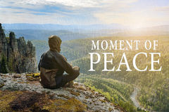Man hiker sitting on top of mountain and contemplates beautiful view to the valley. Moment of Peace lettering. Man hiker sitting on top of mountain and Royalty Free Stock Photo