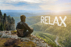 Man hiker sitting on top of mountain and contemplates beautiful view to the valley. Relax lettering in form of clouds. Man hiker sitting on top of mountain and Stock Photo