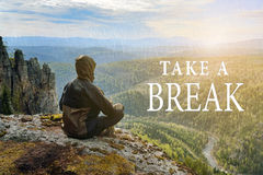 Man hiker sitting on top of mountain and contemplates beautiful view to the valley. Take a Break lettering. Man hiker sitting on top of mountain and Stock Photo