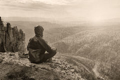 Man hiker sitting on top of mountain in meditation pose and thinking, black and white toned picture.