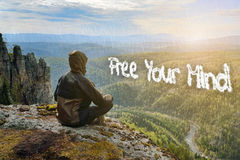 Man hiker sitting on top of mountain meeting sunrise. Free Your Mind inscription sign in form of clouds. Stock Photography