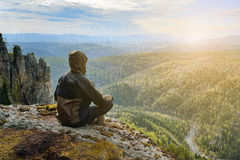 Man hiker sitting on top of mountain meeting sunrise, in harmony with nature.  royalty free stock image