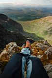 Man hiker sitting on the top of mountain rocks. Beautiful weather with Scotland nature. Detail of hiking boots on the difficult pa. Thway, trail, Friends in the royalty free stock images