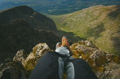 Man hiker sitting on the top of mountain rocks. Beautiful weather with Scotland nature. Detail of hiking boots on the difficult pa. Thway, trail, Friends in the royalty free stock photos