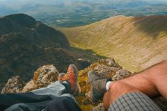Man hiker sitting on the top of mountain rocks. Beautiful weather with Scotland nature. Detail of hiking boots on the difficult pa. Thway, trail, Friends in the royalty free stock image