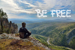 Man hiker sitting on top of mountain and see a sign on sky. Lettering Be Free. Freedom concept.  Stock Photos