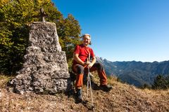Man hiker sitting on the top of mountain. And smile to the camera royalty free stock photos