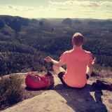 Man hiker sitting on the top of the mountain in yoga pose. Leisure in harmony with nature zen trekker traveler tourism thinking sunset sunrise successful stone royalty free stock photography