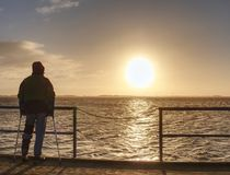 Man hiker stand alone and watching sunrise above sea bridge royalty free stock photo