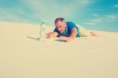 Man hiker suffering from thirst, creeps to a bottle of water Royalty Free Stock Photography
