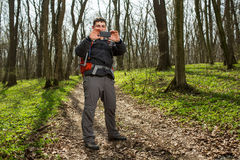 Man hiker taking photo with smart phone in forest. Man hiker taking photo with smart phone at spring forest Stock Images