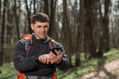 Man hiker taking photo with smart phone in forest Stock Photo