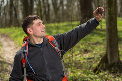 Man hiker taking photo with smart phone in forest Stock Image