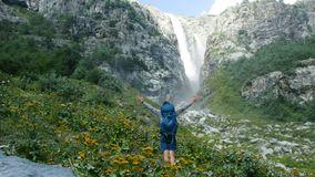 Man hiker tourist with a backpack rises uphill and raises hands up against the backdrop of a huge waterfall in the. Man hiker tourist with a backpack rises stock photo