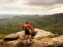 Man hiker with trekking poles and backpack on a top of a mountain. Traveler with Backpack stock photos
