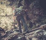 Man hiker walking across stream Stock Photo