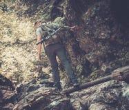 Man hiker walking across stream. In mountain forest stock photo