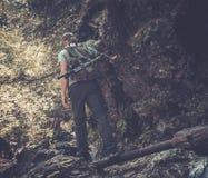 Man hiker walking in a forest. Man hiker walking across stream in mountain forest stock image