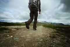 Man hiker walking towards mountain Stock Photos