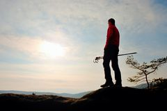 Free Man Hikerwith Trakking Poles Stand On Mountain Peak Rock. Small Pine Bonsai Tree Grows In Rock, Spring Day Stock Photography - 67839532
