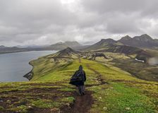 Man hiking alone into the wild admiring volcanic landscape with heavy backpack. Travel lifestyle adventure wanderlust concept royalty free stock images