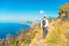Man hiking along beautiful coastal trail. Young caucasian man wearing white shirt, cap and backpack walking along Path of Gods trail on Amalfi coast on sunny royalty free stock photography