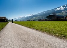 Man hiking along a oountry road in a mountain valley in Switzerland with a great view. Of spring arriving royalty free stock images