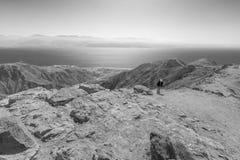 Man hiking ascending desert mountain trail B&W. Stock Images