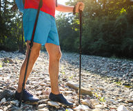 Man hiking with backpac and sticks in mountains Royalty Free Stock Image