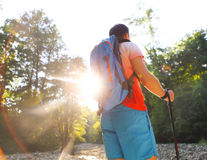 Man hiking with backpac and sticks in mountains in sunset Stock Photos
