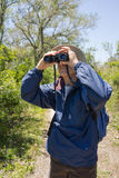 Man Hiking, Birdwatching and Looking Through Binoc. Mature man in hat, backpack and windbreaker standing on a path in an arid landscape looking through Stock Photo