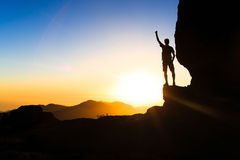 Man hiking climbing silhouette success in mountains sunset Royalty Free Stock Image