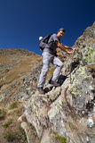 Man hiking on difficult mountain trail Stock Photo