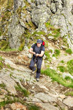 Man hiking on difficult mountain trail with hanging cable Royalty Free Stock Image