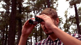 Man hiking through a forest using binoculars stock footage