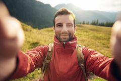 Man in hiking gear taking a selfie outside. Young man in hiking gear standing outside taking a selfie with mountains behind him while out trekking in the Stock Photography