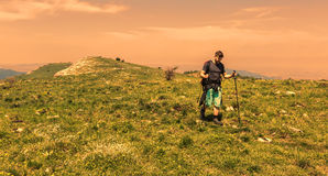 Man Hiking in Green Mountains. Young man with nordic sticks hiking at the dusk in Apuseni Mountains in Transylvania,Romania Royalty Free Stock Photography